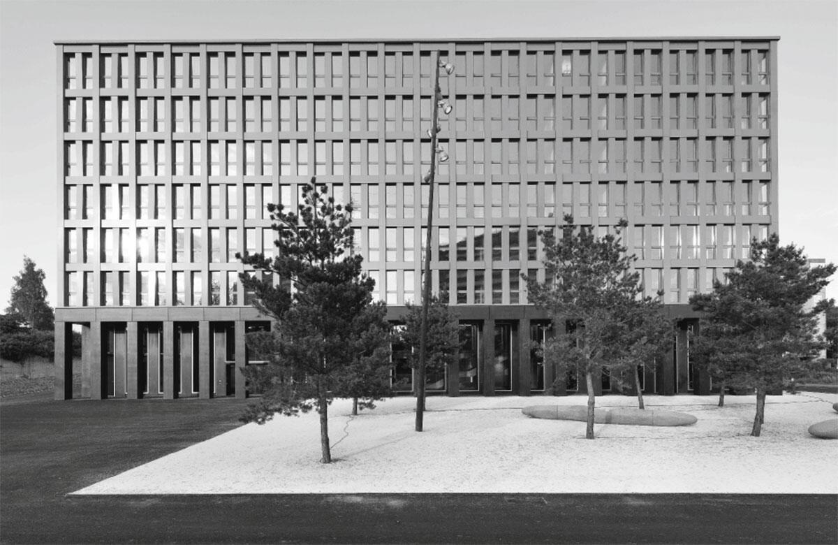Das Verwaltungsgebäude BIT ist ein Bürohaus mit vorgelagertem Park, Teil einer mäandrierenden Reihe ähnlicher Bauten.
