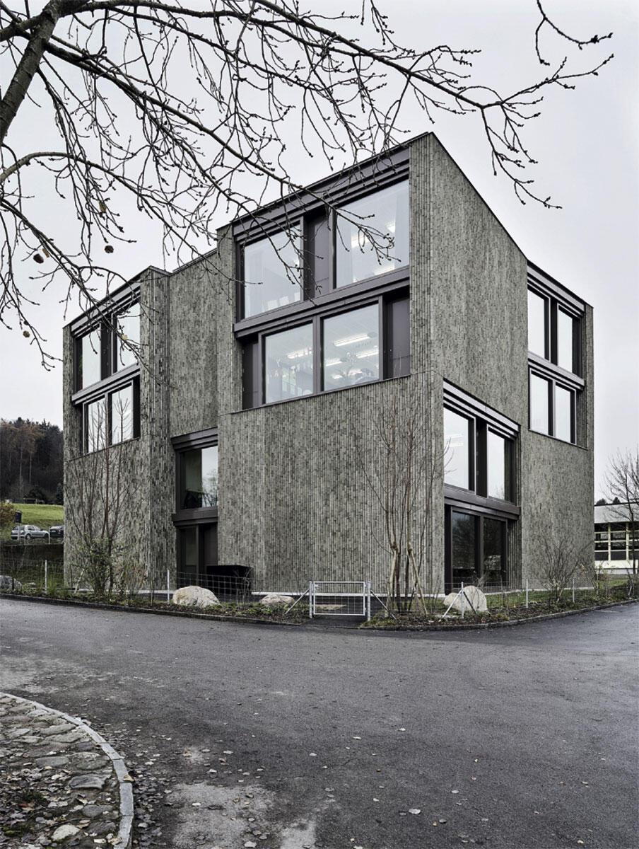 Die vertikal aufkragenden Backsteine bringen ihren nicht tragenden Einsatz als Oberfläche von mächtigen Betonelementen zur Sprache: Schulhaus Kopfholz in Adliswil von Boltshauser Architekten.