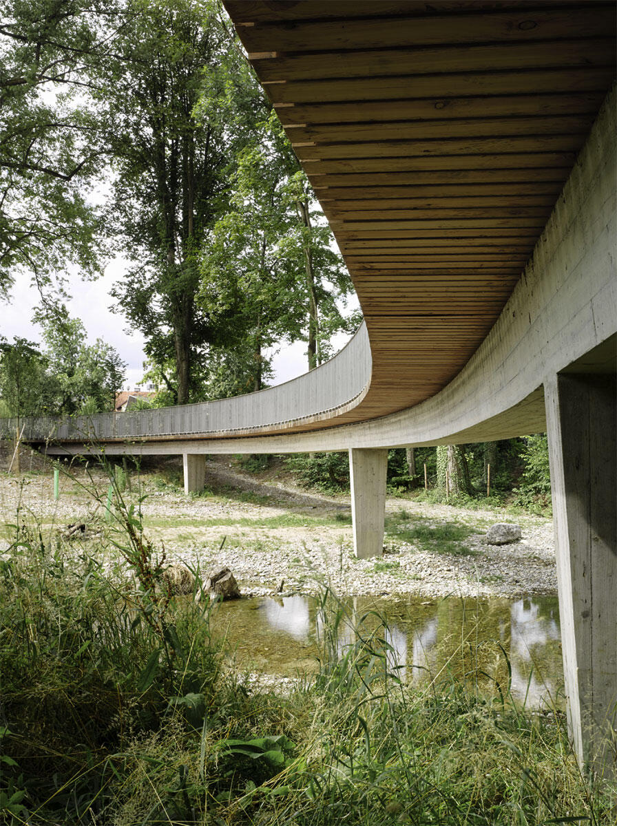 Die Schwarzpappelbrücke überquert in doppeltem Schwung den Altlauf der Murg und macht ihn so erlebbar. Eine schlanke Betonkonstruktion trägt die auskragende Balkenlage des Gehwegs. Architektur: Staufer & Hasler Architekten, St. Gallen