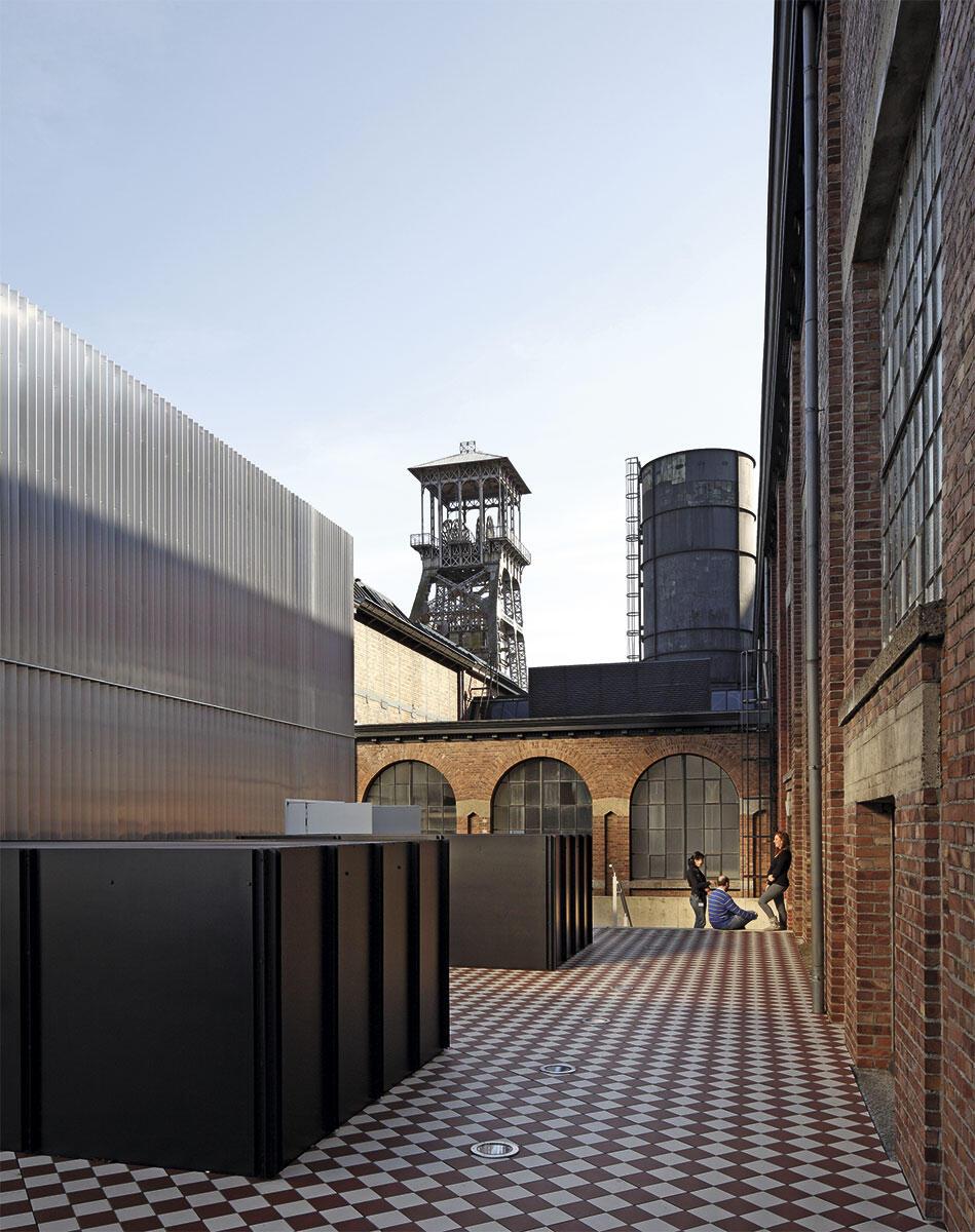 Umlaufende Terrassenflächen des Kulturzentrums C-Mine in Genk machen das reizvolle Nebeneinander von neuen Theatersälen und der alten Energiezentrale erfahrbar.