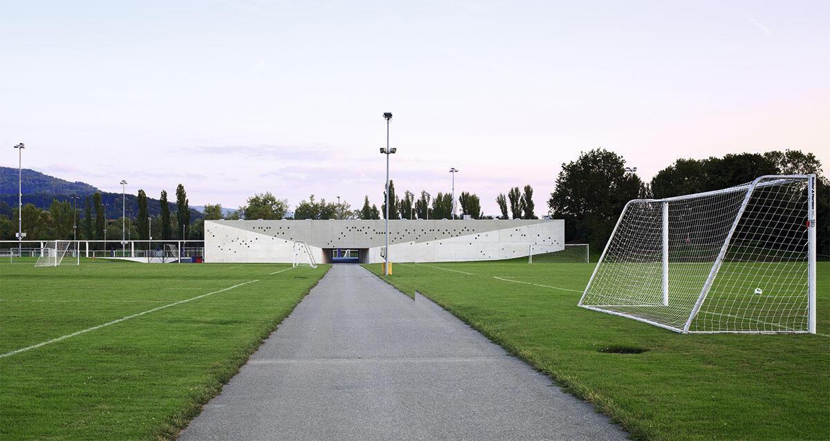 Im Pathos des axialen Zugangs, im Tor- und im Tempelmotiv spielen im öffentlichen Fussball-Nachwuchscampus des FC Basel zentrale Motive des Sakralen zusammen.
