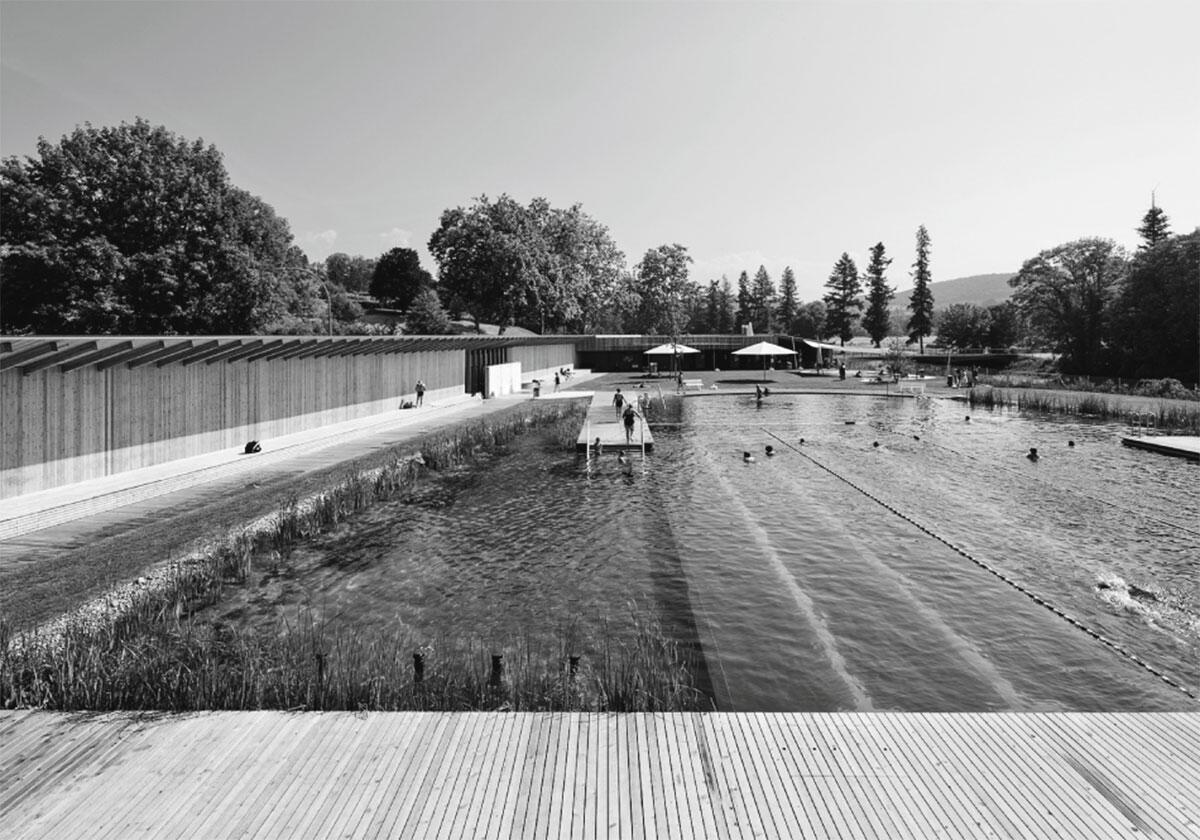 Das ovale Becken wird von Holzwänden und -bauten eingefasst, sodass sich alle Blicke auf die Mitte fokussieren: Naturbad in Riehen von Herzog & de Meuron.