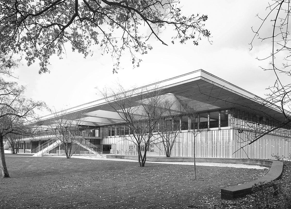 Das Dach des Sportzentrums kragt weit über die offen gestaltete Eingangszone aus und bildet einen repräsentativen Ort. Die Fassade und Untersicht aus Holz verbinden sich mit Terrasse und Freitreppe zu einem stimmigen Hintergrund für das Freibad. Bild: Filip Dujardin