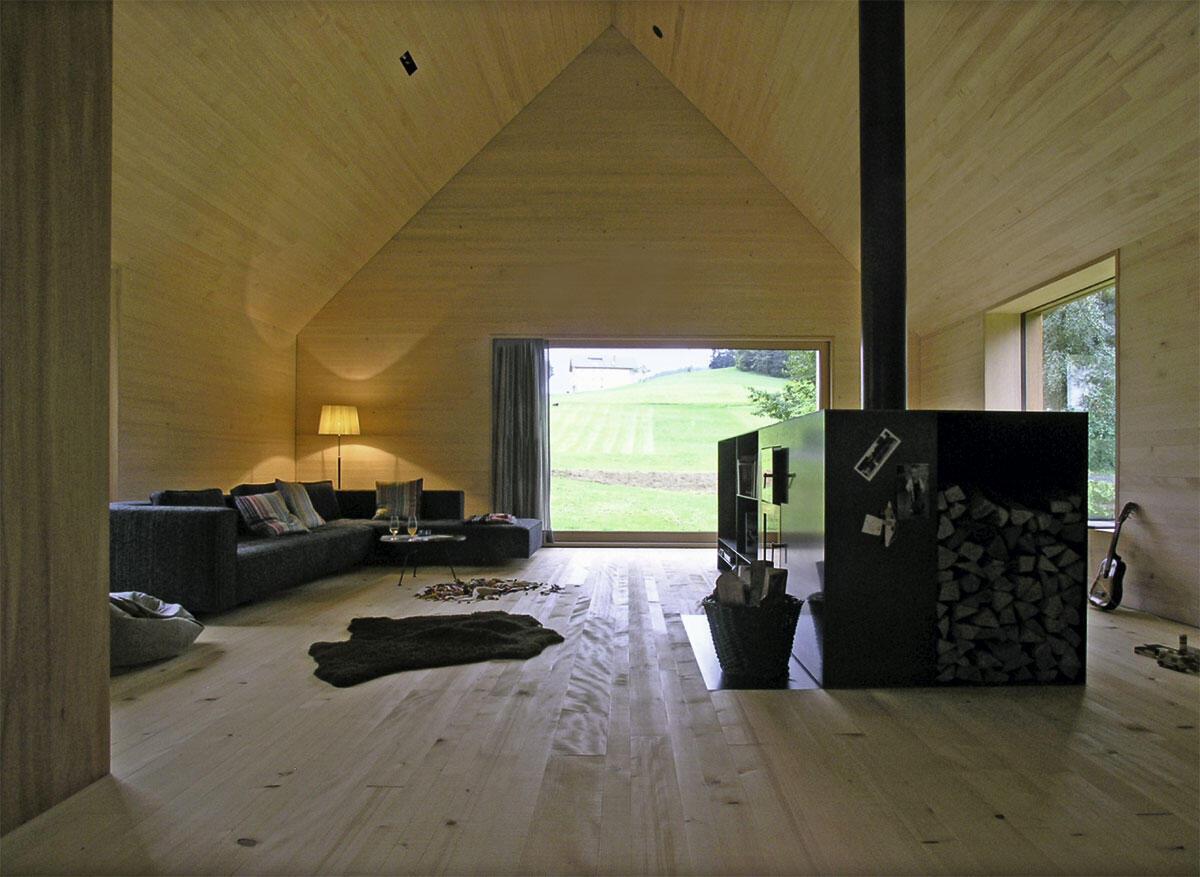 Im hohen Wohnzimmer ist das behagliche Kleid aus familieneigenem Holz in seiner archaischen Zeltform am besten spürbar. Der gravitätische Ofen aus Schwarzstahl zoniert den Raum.