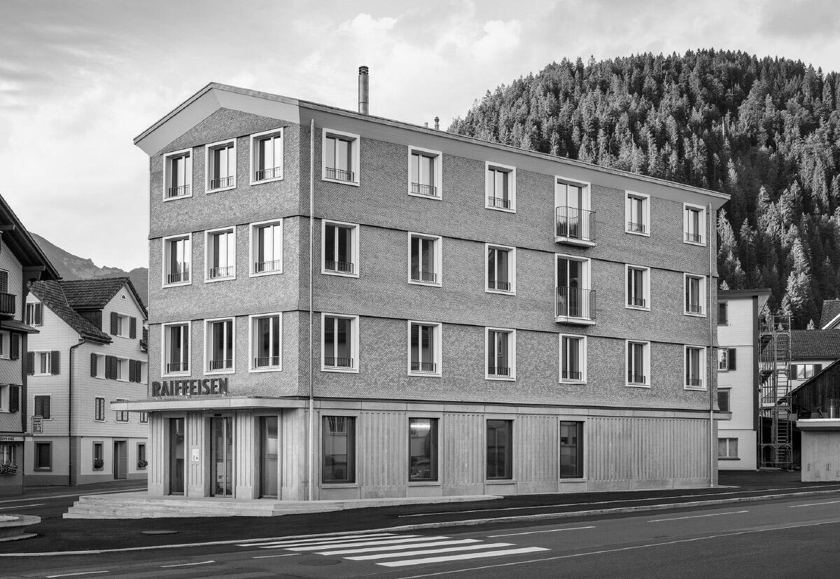 Vom runden Dorfbrunnen geht es ein paar Stufen hoch zur repräsentativen Eingangshalle der Bank. Aufgrund der präzisen Detaillierung in Beton und Holz stellt sich eine wohnlich-repräsentative Stimmung ein. Bild: Markus Kaech
