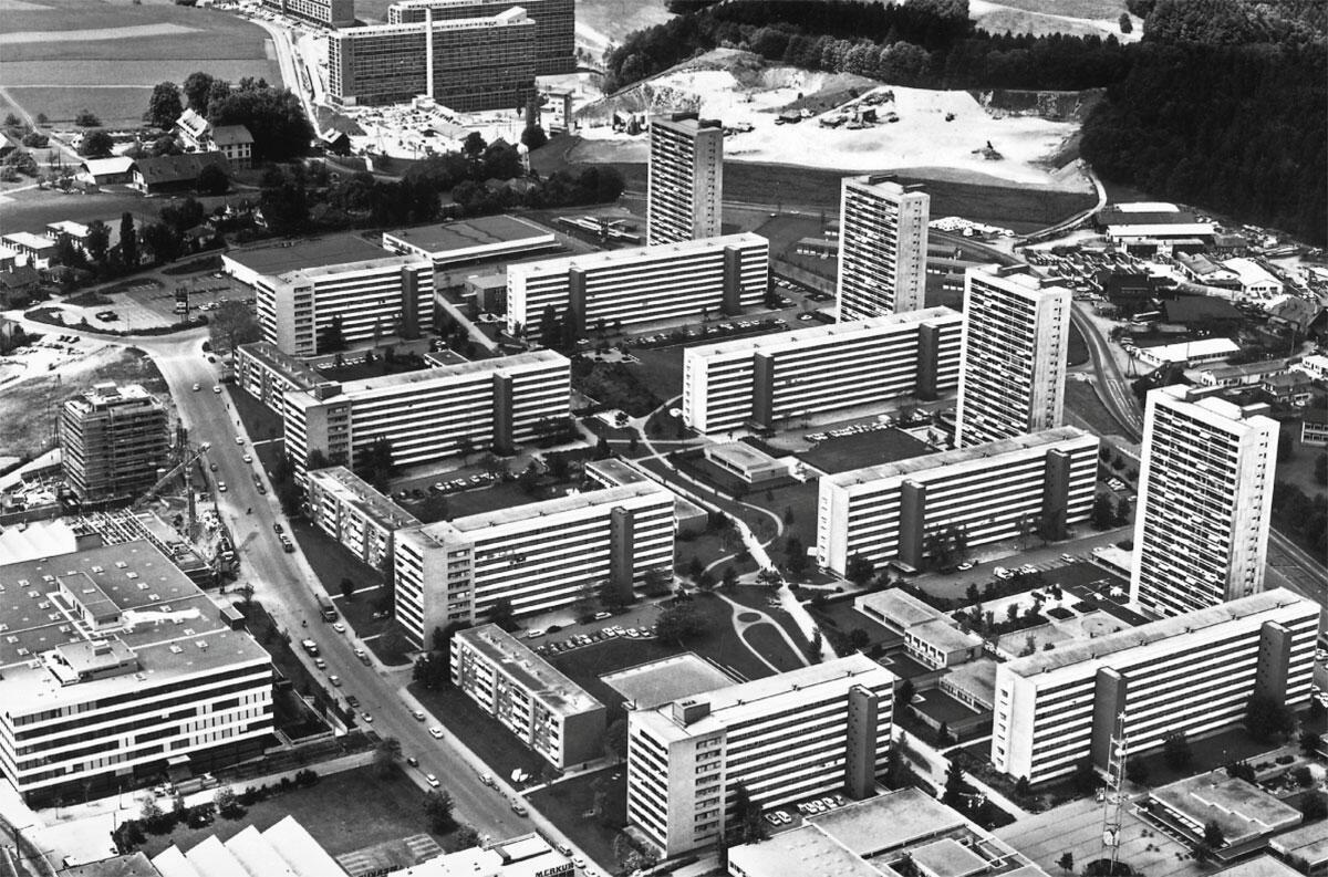 Das Tscharnergut 1966, kurz nach der Fertigstellung. Zwischen die Scheiben- und Punkthochhäuser schieben sich niedrige Wohnhäuser und die Flachbauten des Ladenzentrums (Vordergrund). Links die gleich zeitig geplante Gewerbezone, im Hintergrund die Scheiben der Wohnsiedlung Gäbelbach.