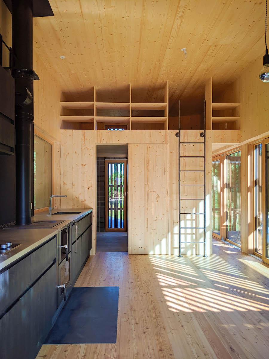 Der Hauptraum geniesst eine grosszügige Raumhöhe, rückseitig liegen die Zimmer.