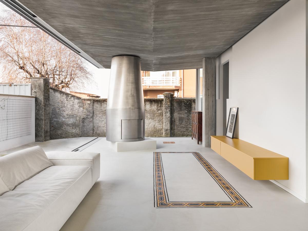 Der neue, dreiseitig verglaste Anbau mit Kamin bildet das Wohnzimmer, offen wie eine Veranda.