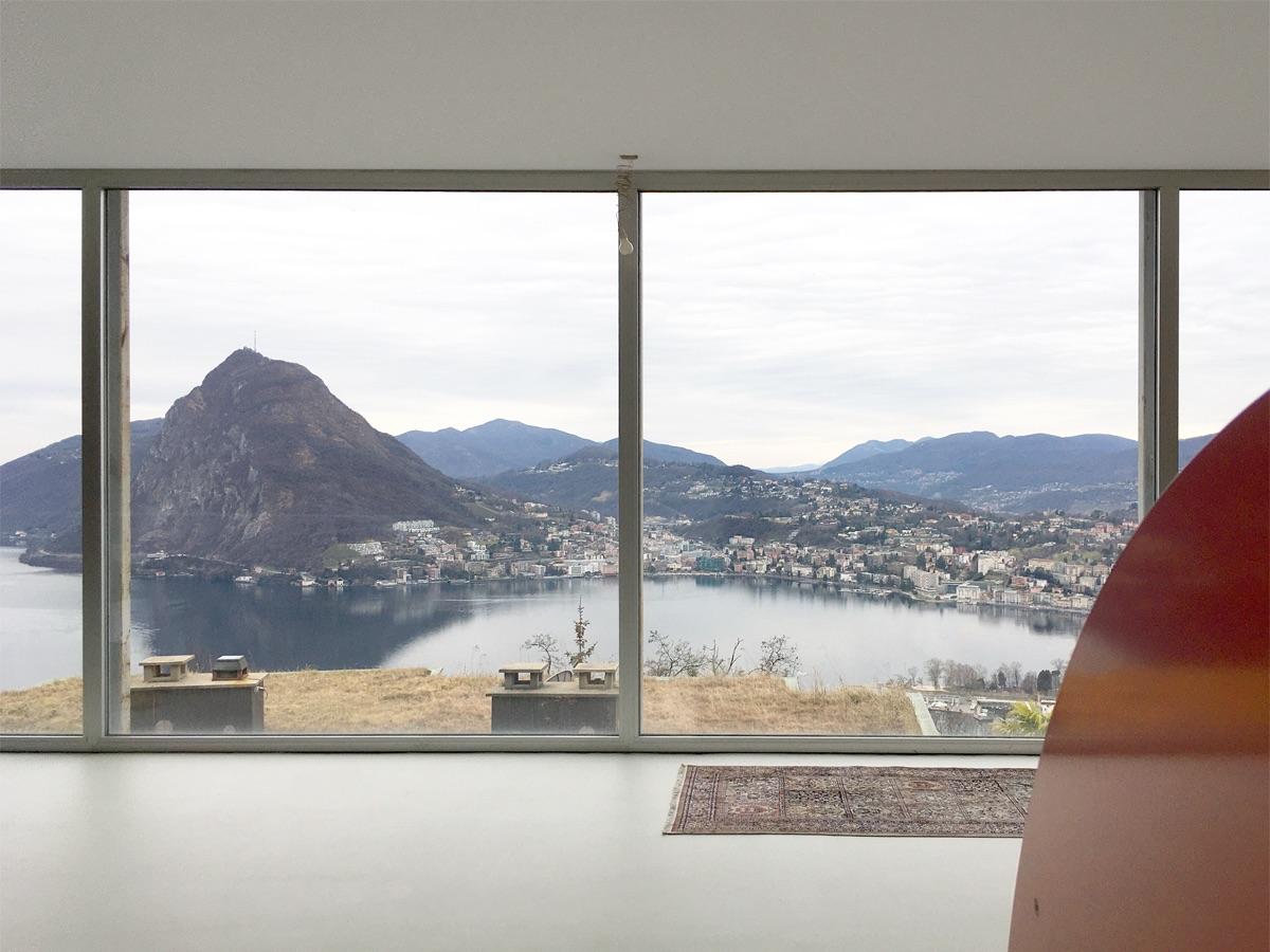 Im grosszügig verglasten Wohnzimmer weitet sich der Blick über den Lago di Lugano.