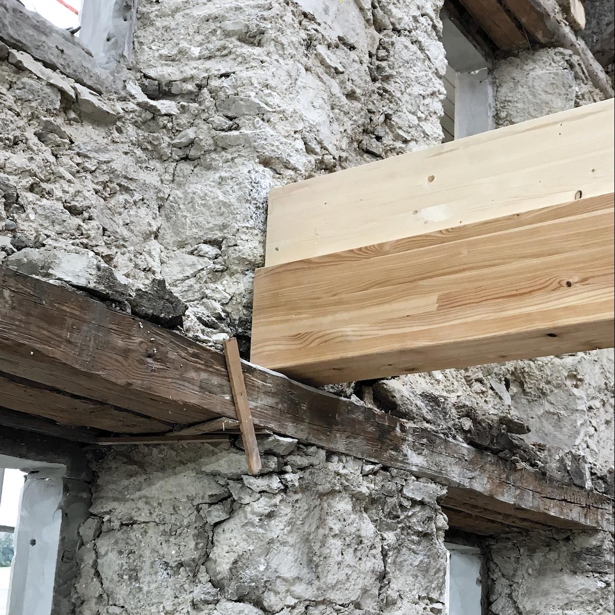 In die alte Hülle wurde eine neue Holzbaustruktur eingefügt: neue Balken auf alte Mauern gelegt.