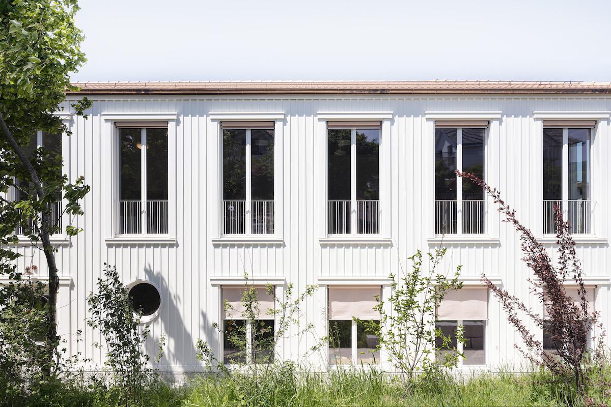 Das Schulgebäude ist in strahlend weisses Holz gehüllt.
