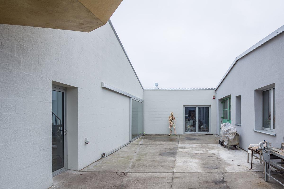Der Hof verbindet das neue Atelier mit der bestehenden Gewerbehalle seines Vaters.