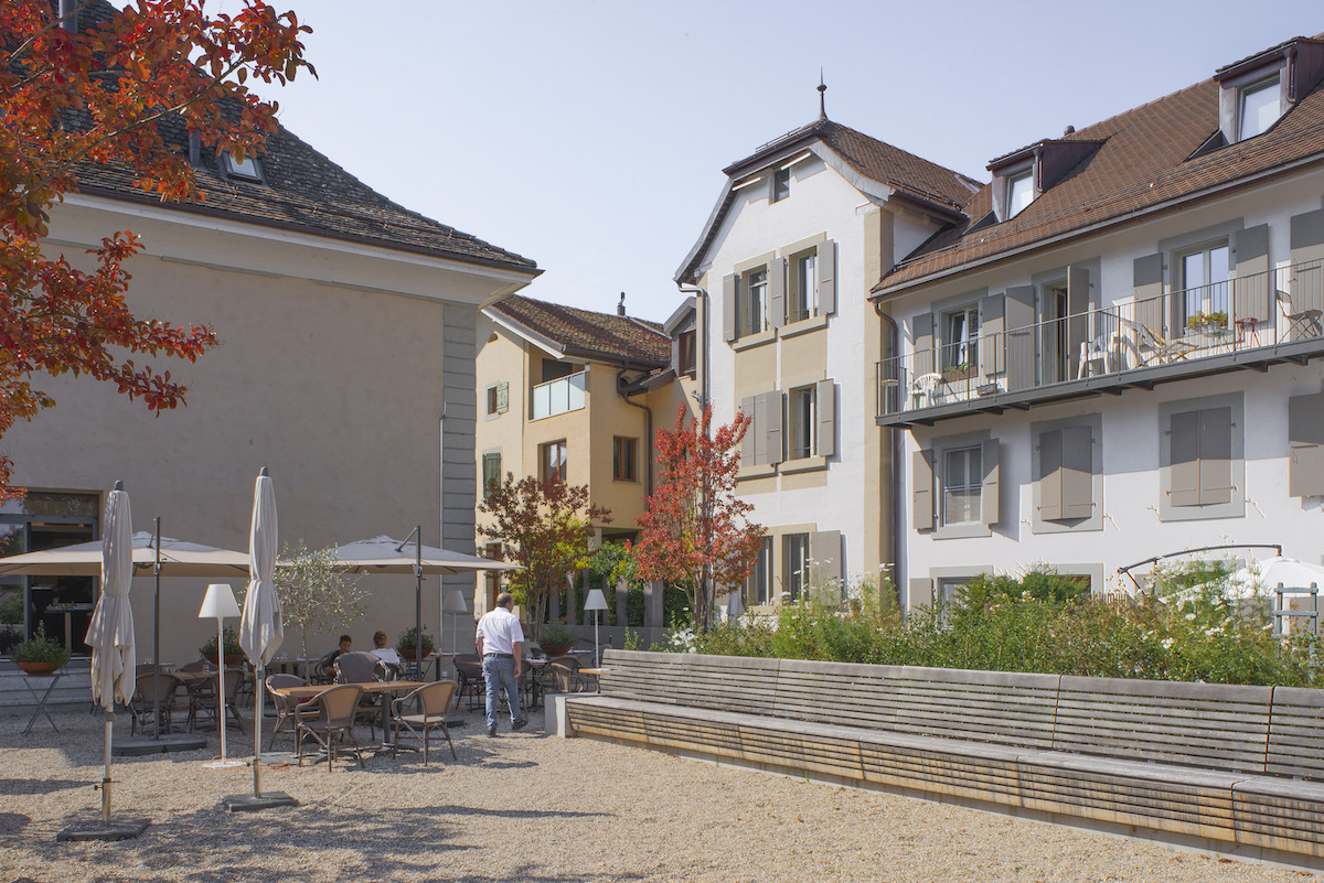 Aus der «Auberge communale» wurde ein Restaurant und Hotel mitten im Dorf (2011; Architektur: atelier d'architecture PA Couvreu). Der Abriss eines Nebengebäudes macht einem Dorfplatz und der Restaurantterrasse Platz (2016, Landschaftsarchitektur: L'Atelier du Paysage Jean-Yves le Baron). Bild: Pierre Marmy